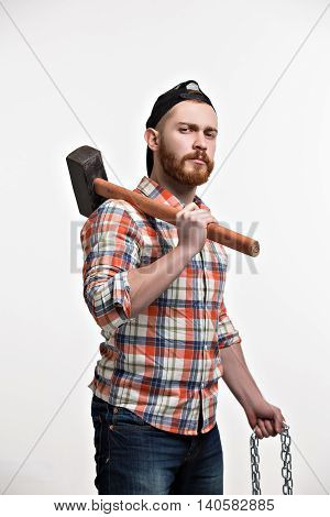Portrait of serious bearded man in cap and checked shirt holding hammer while looking at camera.Studio shot
