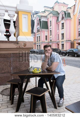 Handsome man sitting at wooden table in outdoor vegan cafe and looking at camera. Man waiting for his order or friends.