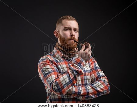 Portrait of handsome bearded man in checked shirt smoking pipe and looking at camera. Studio shot. Isolated