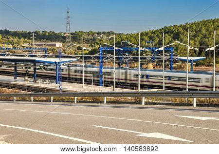 Modern high speed train departs from railway station with natural motion blur effect and beautiful landscape. Camp de Tarragona Spain. Horizontal.