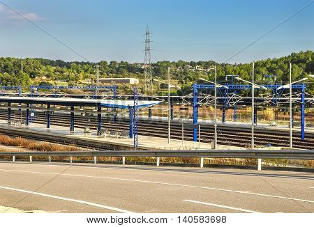 View on platforms of modern railway station in Tarragona (Spain) with beautiful landscape. Horizontal.