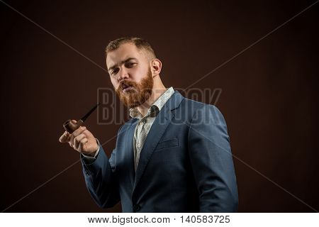 Portrait of handsome confident man in suit holding smoking pipe against of brown background.Isolated.