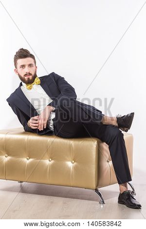 Portrait of handsome man relaxing on modern pouffe in elegant suit with bow-tie