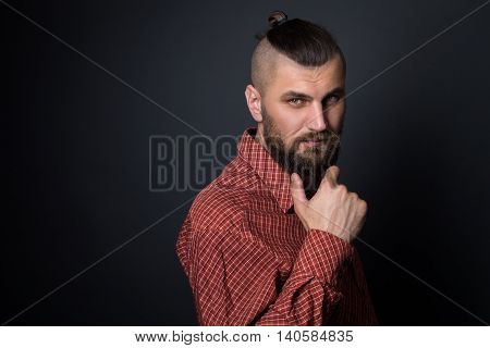 bearded man hold his beard with a very interesting look