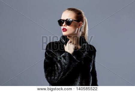 Portrait of blonde model with red lips wearing black fur coat and sunglasses looking away.Isolated.Grey background.
