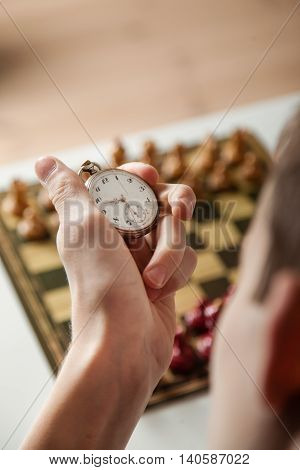 Person Holding Stop Watch Above Chess Board