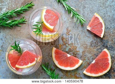 Grapefruit and rosemary drink, alcohol or non-alcohol cocktail or infused water with ice