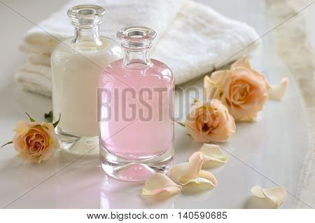 Cosmetic liquids maybe milk shampoo or toner in glass bottles decorated with roses.