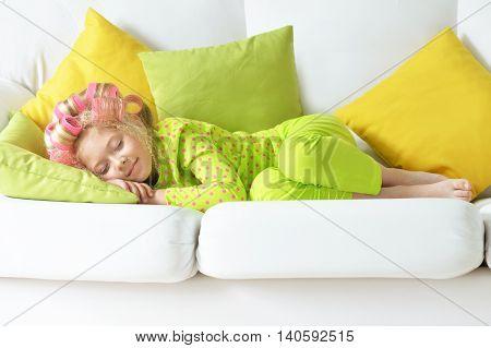 Happy cute little girl in hair curlers sleeping on sofa