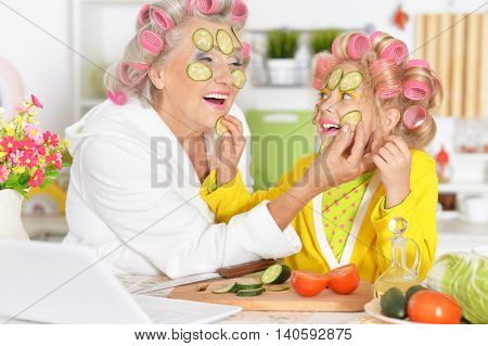 Senior woman and granddaughter at kitchen with  vegetables