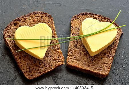 Two slices of bread with a heart shaped butter