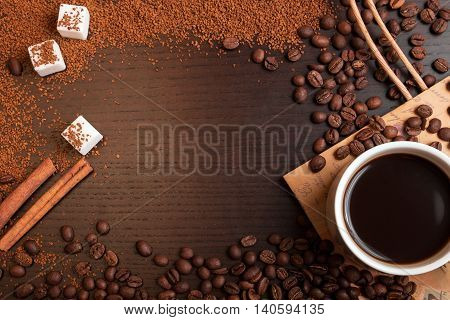 Cup of coffee coffee beans ground coffee sugar and cinnamon on dark brown table