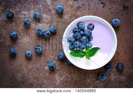 Light greek yogurt or cream dessert with fresh blueberries served in white bowl top view stylized photo