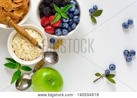 Healthy breakfast with cottage cheese or ricotta fruits berries and cereals top view background