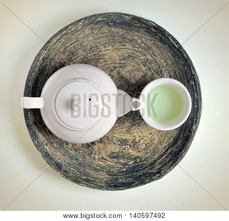Stylized photo of white tea pot and tea cup on a rustic dish green tea concept top view