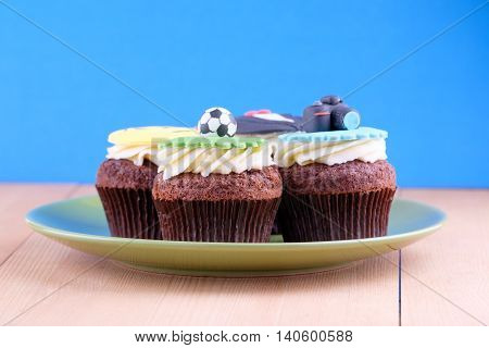 Delicious cupcakes with icons of ball tuxedo smiley and camera on it with green plate on wooden desk and blue background