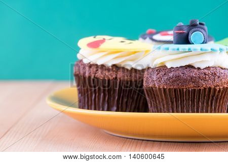 Delicious cupcakes with icons of ball tuxedo smiley and camera on it with yellow plate on wooden desk and green background