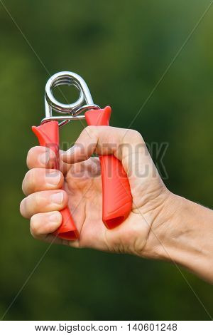 hand doing exercises with hand grip on blurred background
