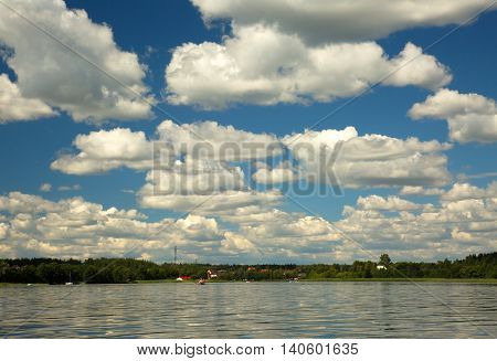 Summer landscape with blue sky with many white clouds and surface of Karsinskie lake in Bory TucholskiePoland. Horizontal view.