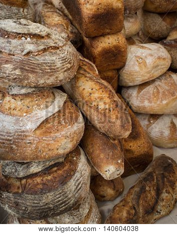 Many different types of fresh bakery bread in background