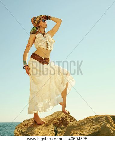 Fashion shot of a beautiful boho style woman standing on a rock near sea. Boho outfit, hippie, indie style, copy space for text