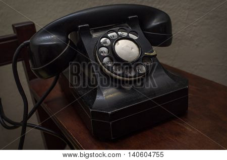 Old vintage rotary dial telephone on wooden desk