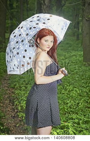 View of a young girl standing in summer forest with umbrella