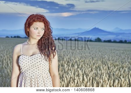 Young girl standing in a cornfield with sky in the background