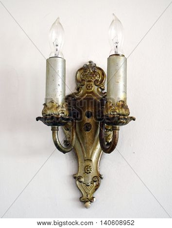 Antique brass wall sconce on white wall - isolated