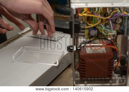 Technician bends acrylic glass for electronics trim
