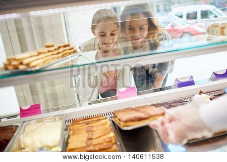 Daughter and her mother choose sweets in beautiful candy store