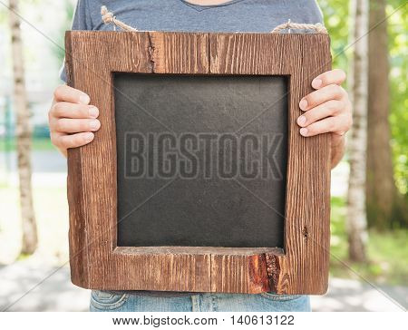 Man Holding Empty Wooden And Slate Board. Template Mock Up