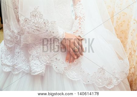 Lace white wedding dress with long sleeves. Women's hands. wedding ring