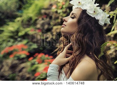Portrait of a brunette beauty in tropical garden
