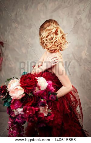 Sexy stylish blonde beautiful woman on the sofa. bouquet of flowers, peonies, pompons. Red dress.