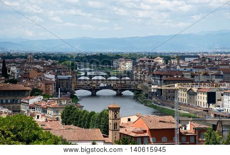 View of medieval stone bridge Ponte Vecchio and the Arno river in Florence Tuscany Italy.