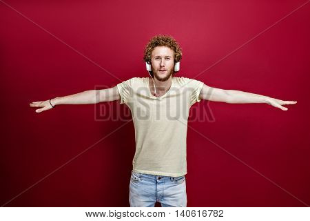 Portrait of young curly-haired man listening to music via headphones with outstretched arms.Isolate.