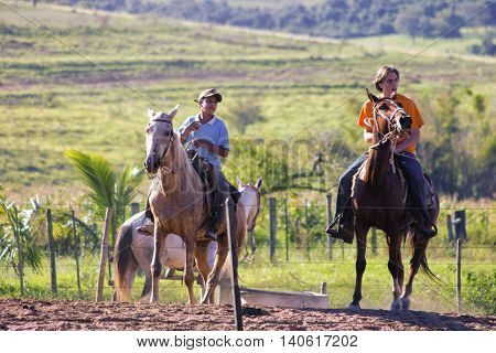 City, State, Brazil - April 30, 2006: Farm boys riding a horse in Herculandia - Sao Paulo, Brazil.
