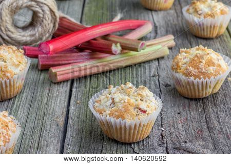 Rhubarb muffin in paper cups with rhubarb petioles in the background on Old Wooden Board