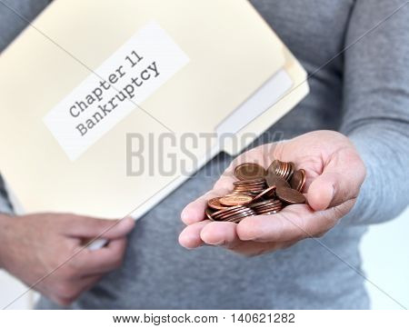 Man holding loose coins & folder with bankrutpcy documents