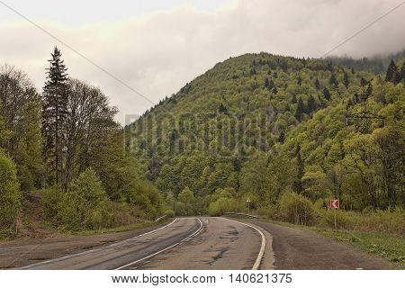 Lonely road in May cloudly Carpathians. Ukraine
