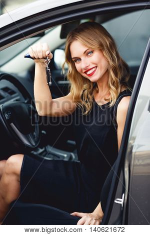 Elegant smiling young business woman in black summer dress sitting in car and holding keys. Split toned photo