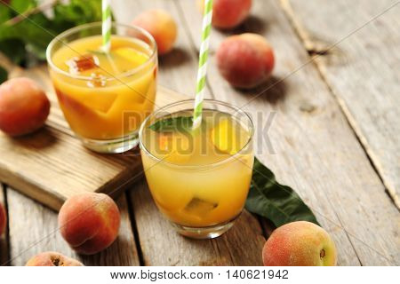 Glasses Of Peach Juice On Grey Wooden Table