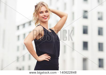 Elegant blonde girl with curly hair on white houses background in ponytail. Split toned photo