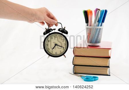Study time preparations with alarm-clock in women's hand
