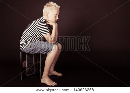 Pensive Boy Rest Hands On Knees While Sitting