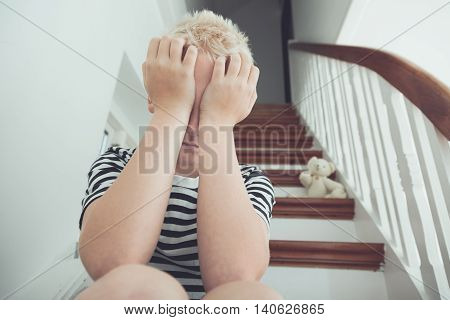 Blond Boy Pressing Hands To Face With Teddy Bear