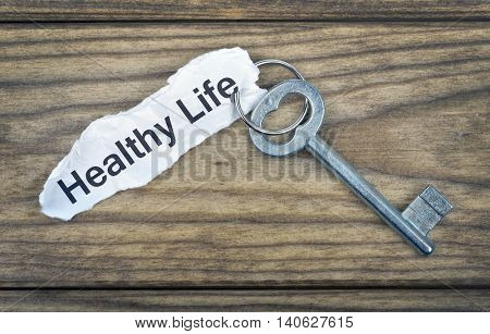 Key with message Healthy Life on wooden table