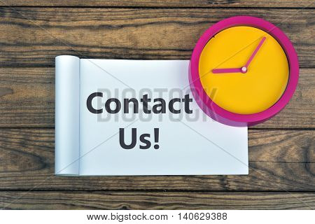 Clock and word Contact Us on wooden table