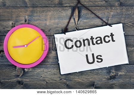 Contact  us sign and clock on wooden table